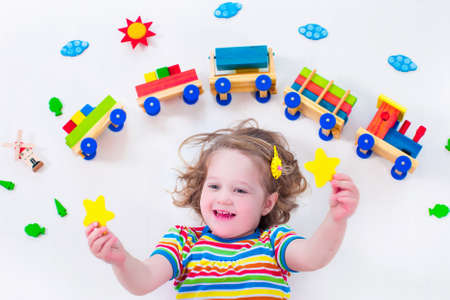 Foto de Child playing with wooden train. Toy railroad for kids. Toddler kid at day care. Educational toys for preschool and kindergarten child. Little girl at daycare. - Imagen libre de derechos