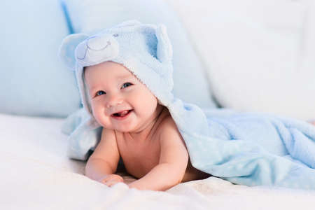 Baby boy wearing diaper and blue towel in white sunny bedroom. Newborn child relaxing in bed after bath or shower. Nursery for children. Textile and bedding for kids. New born kid with toy bear.