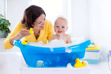 Photo pour Happy baby taking a bath playing with foam bubbles. Mother washing little boy. Young child in a bathtub. Smiling kids in bathroom with toy duck. Mom bathing infant. Parent and kid play with water. - image libre de droit