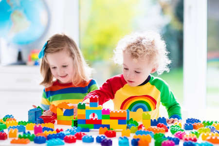 Foto de Child playing with colorful toys. Little girl and funny curly baby boy with educational toy blocks. Children play at day care or preschool. Mess in kids room. Toddlers build a tower in kindergarten. - Imagen libre de derechos