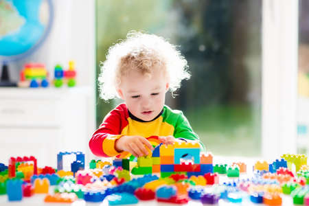 Child playing with colorful toys sitting at a window. Little curly boy with educational toy blocks. Children play at day care or preschool. Mess in kids room. Toddlers build a tower in kindergarten.
