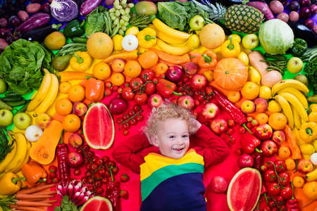 Foto für Little boy with variety of fruit and vegetable. Colorful rainbow of raw fresh fruits and vegetables. Child eating healthy snack. Vegetarian nutrition for kids. Vitamins for children. View from above. - Lizenzfreies Bild