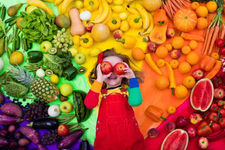 Foto de Little girl with variety of fruit and vegetable. Colorful rainbow of raw fresh fruits and vegetables. Child eating healthy snack. Vegetarian nutrition for kids. Vitamins for children. View from above. - Imagen libre de derechos