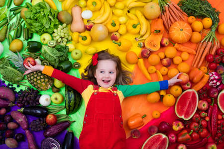 Foto für Little girl with variety of fruit and vegetable. Colorful rainbow of raw fresh fruits and vegetables. Child eating healthy snack. Vegetarian nutrition for kids. Vitamins for children. View from above. - Lizenzfreies Bild