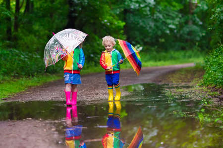 Little boy and girl play in rainy summer park. Children with colorful rainbow umbrella, waterproof boots jump in puddle and mud in the rain. Kids walk in autumn shower. Outdoor fun by any weatherの写真素材