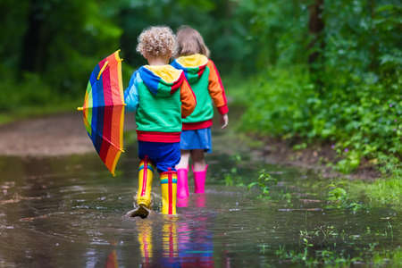 Foto de Little boy and girl play in rainy summer park. Children with colorful rainbow umbrella, waterproof boots jump in puddle and mud in the rain. Kids walk in autumn shower. Outdoor fun by any weather - Imagen libre de derechos