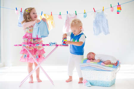 Photo pour Newborn child on pile of clean dry towels. Brother and sister playing with little sibling. Siblings bonding. Children ironing clothes. Twin kids play with baby boy. New born kid after bath in a towel - image libre de droit