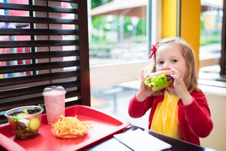 Photo pour Little girl eating hamburger and French fries in a fast food restaurant. Child having sandwich and potato chips for lunch. Kids eat unhealthy fat food. Grilled fastfood sandwich for children. - image libre de droit
