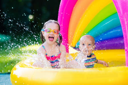Photo pour Children playing in inflatable baby pool. Kids swim and splash in colorful garden play center. Happy boy and girl playing with water toys on hot summer day. Family having fun outdoors in the backyard. - image libre de droit