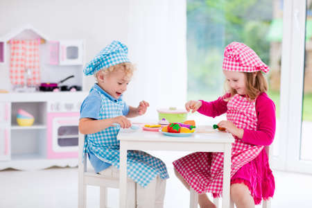 Photo pour Little girl and boy in chef hat and apron cooking in toy kitchen. Educational toys for young children. Kids play, cut wooden vegetables and cook. Toddler kid playing with stove, pans and dishes. - image libre de droit