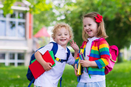 Photo for Child going to school. Boy and girl holding books and pencils on the first school day. Little students excited to be back to school. Beginning of class after vacation. Kids eating apple in school yard - Royalty Free Image