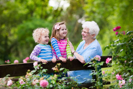 Photo pour Happy senior lady playing with little boy and girl in blooming rose garden. Grandmother with grand children sitting on a bench in summer park with beautiful flowers. Kids gardening with grandparent. - image libre de droit