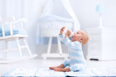 Photo pour Adorable baby boy playing on a blue floor mat and drinking milk from a bottle in a white sunny nursery with rocking chair and bassinet. Bedroom interior with infant crib. Formula drink for infant. - image libre de droit