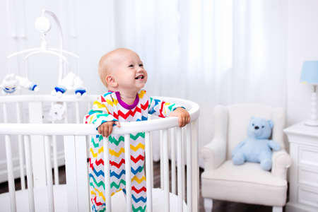 Foto de Cute laughing baby standing in bed after nap time. Nursery interior for young kids. Adorable little boy playing in his crib. White furniture for children bedroom. - Imagen libre de derechos