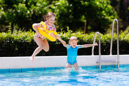 Photo pour Happy little girl and boy holding hands jumping into outdoor swimming pool in a tropical resort during family summer vacation. Kids learning to swim. Focus on boy. - image libre de droit