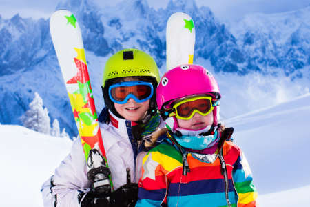 Boy and girl skiing in mountains. Toddler kid and teenager with helmet, goggles, poles. Ski race for children. Winter sport for family. Kids ski lesson in alpine school. Little skier racing in snowの写真素材