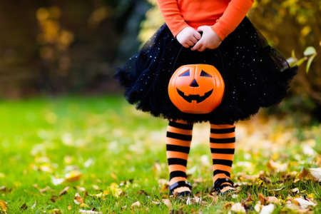 Foto de Little girl in witch costume playing in autumn park. Child having fun at Halloween trick or treat. Kids trick or treating. Toddler kid with jack-o-lantern. Children with candy bucket in fall forest. - Imagen libre de derechos