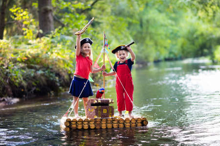 Photo pour Kids dressed in pirate costumes and hats with treasure chest, spyglasses, and swords playing on wooden raft sailing in a river on hot summer day. Pirates role game for children. Water fun for family. - image libre de droit