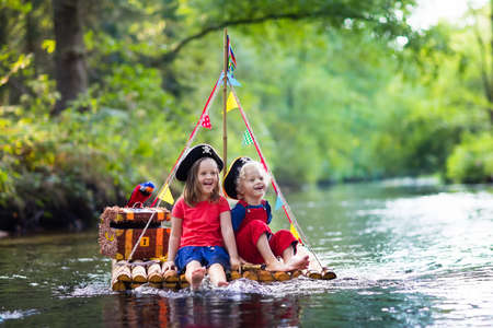 Photo for Kids dressed in pirate costumes and hats with treasure chest, spyglasses, and swords playing on wooden raft sailing in a river on hot summer day. Pirates role game for children. Water fun for family. - Royalty Free Image