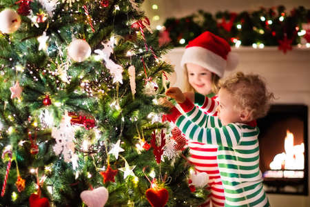Happy little kids in matching red and green striped pajamas decorate Christmas tree in beautiful living room with traditional fire place. Children opening presents on Xmas eve.の写真素材