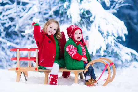 Little girl and baby boy enjoying a sleigh ride. Child sledding. Toddler kid riding a sledge. Children play outdoors in snow. Kids sled in snowy park. Outdoor winter fun for family Christmas vacation.の写真素材