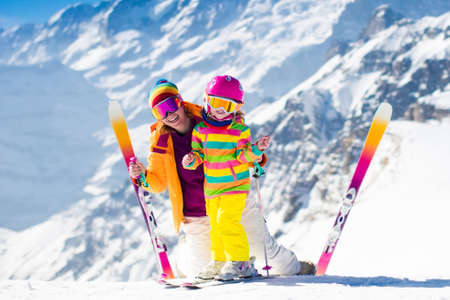 Family ski vacation. Group of skiers in Swiss Alps mountains. Mother and child skiing in winter. Parents teach kids alpine downhill skiing. Ski gear and wear, safe helmets.