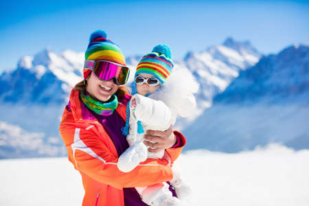 Photo pour Young mother and little baby enjoying winter ski vacation in alpine resort. Eyewear and sun protection sunglasses for infants. Family with safe goggles walking in the snow in the Alps mountains. - image libre de droit