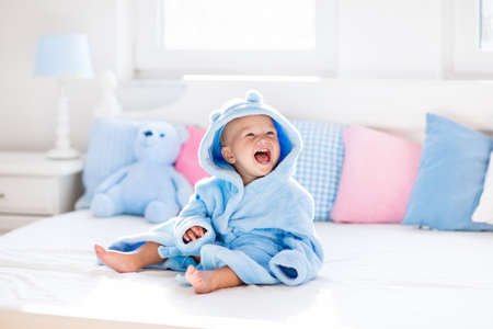 Foto de Cute happy laughing baby boy in soft bathrobe after bath playing on white bed with blue and pink pillows in sunny kids room. Child in clean and dry towel. Wash, infant hygiene, health and skin care. - Imagen libre de derechos