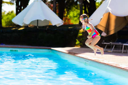 Foto de Happy little girl with inflatable toy ring jumping into outdoor swimming pool in a tropical resort during family summer vacation. Kids learning to swim. Water fun for children. - Imagen libre de derechos