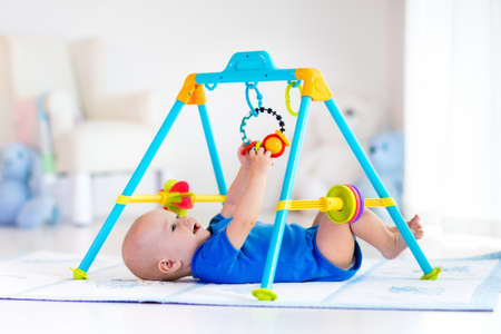 Foto de Cute baby boy on colorful playmat and gym, playing with hanging rattle toys. Kids activity and play center for early infant development. Newborn child kicking and grabbing toy in white sunny nursery - Imagen libre de derechos