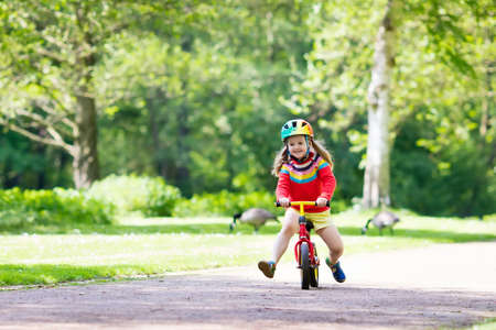 Child riding balance bike. Kids on bicycle in sunny park. Little girl enjoying to ride glider bike on warm summer day. Preschooler learning to balance on run bicycle in safe helmet. Sport for kids.