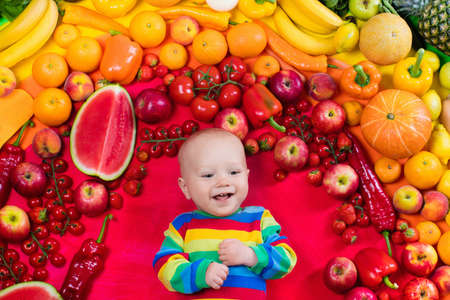 Baby boy with variety of fruit and vegetable. Colorful rainbow of raw fresh fruits and vegetables. Child eating healthy snack. Vegetarian nutrition for kids. Vitamins for children. View from above.の写真素材