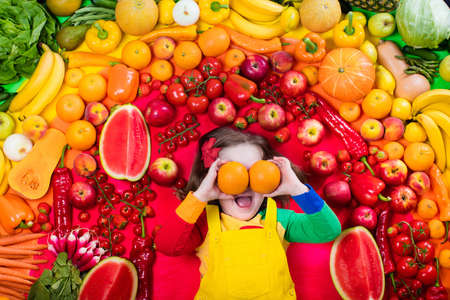 Little girl with variety of fruit and vegetable. Colorful rainbow of raw fresh fruits and vegetables. Child eating healthy snack. Vegetarian nutrition for kids. Vitamins for children. View from above.の写真素材