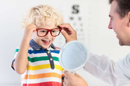 Foto de Child at eye sight test. Little kid selecting glasses at optician store. Eyesight measurement for school kids. Eye wear for children. Doctor performing eye check. Boy with spectacles at letter chart. - Imagen libre de derechos