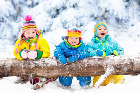 Photo for Kids playing in snow. Children play outdoors on snowy winter day. Boy and girl catching snowflakes in snowfall storm. Brother and sister throwing snow balls. Family Christmas vacation activity. - Royalty Free Image