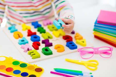 Foto de Child doing homework for school at white desk. Wooden educational abc toy puzzle for kids. Happy back to school student. Kid learning alphabet letters. Little girl with school supplies and books. - Imagen libre de derechos
