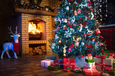Photo pour Christmas home interior with tree and fireplace. Traditional living room in country house decorated with lights and candles. Big stone open fire place. Xmas gifts and presents. Reindeer decoration. - image libre de droit
