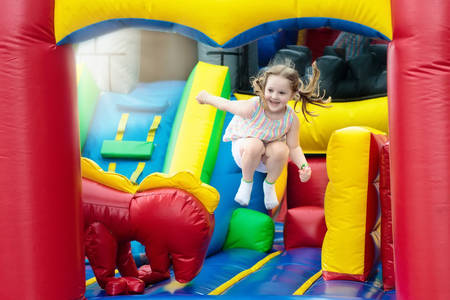 Photo pour Child jumping on colorful playground trampoline. Kids jump in inflatable bounce castle on kindergarten birthday party Activity and play center for young child. Little girl playing outdoors in summer. - image libre de droit