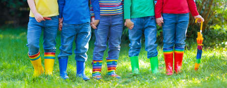 Kids in rain boots. Group of kindergarten children in colorful rubber boots and autumn jackets. Footwear for rainy fall. Foot wear for child and baby. Toddler in wellies. Rainbow gumboots. Kid fashionの写真素材