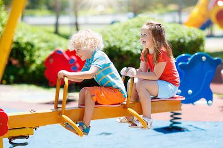 Foto de Kids climbing and sliding on outdoor playground. Children play in sunny summer park. Activity and amusement center in kindergarten or school yard. Child on colorful swing. Toddler kid outdoors. - Imagen libre de derechos