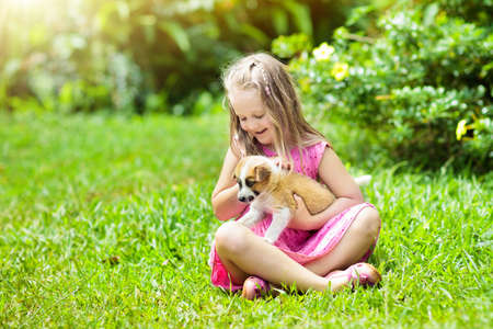 Foto de Kids play with cute little puppy. Children and baby dogs playing in sunny summer garden. Little girl holding puppies. Child with pet dog. Family and pets on park lawn. Kid and animals friendship. - Imagen libre de derechos