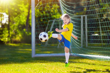 Photo pour Kids play football on outdoor field. Brazil team fans. Children score a goal at soccer game. Little girl in Brazilian jersey and cleats kicking ball. Football pitch. Sports training for player. - image libre de droit