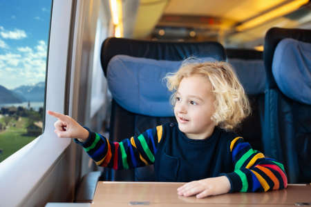 Photo pour Child traveling by train. Little kid in a high speed express train on family vacation in Europe. Travel by railway. Children in railroad car. Kids in rail way wagon. Entertainment for young passenger. - image libre de droit