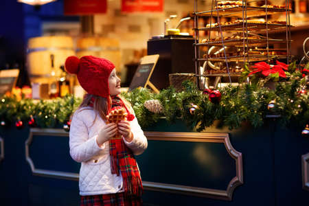 Photo pour Children shopping on traditional Christmas market in Germany on snowy winter day. Kids buying waffle, candy, pastry and gingerbread in fair sweet shop. Little girl choosing sweets in Xmas bakery. - image libre de droit