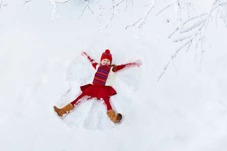 Foto de Child making snow angel on sunny winter morning. Kids winter outdoor fun. Family Christmas vacation. Little girl playing in snow after heavy storm. Active children outdoors on Xmas day. - Imagen libre de derechos