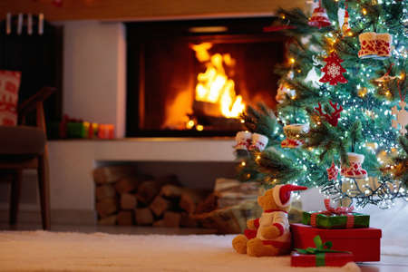Photo pour Christmas tree with presents at decorated fireplace. Family celebration of winter holidays. Living room interior with open fire place and Xmas tree with gifts for kids. - image libre de droit