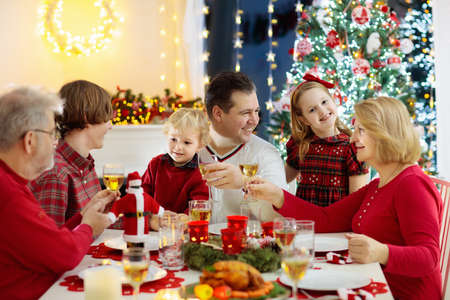 Photo pour Family with children eating Christmas dinner at fireplace and decorated Xmas tree. Parents, grandparents and kids at festive meal. Winter holidays celebration and food. Kids open presents and gifts. - image libre de droit