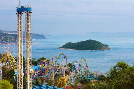 Foto de Ocean theme park in Hong Kong. Roller coaster and entertainment attraction at sea side in amusement theme park in Hong Kong. View from mountain top. - Imagen libre de derechos