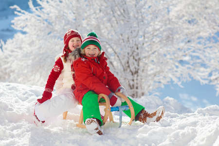 Foto de Little girl and boy enjoying sleigh ride. Child sledding. Toddler kid riding a sledge. Children play outdoors in snow. Kids sled in snowy park in winter. Outdoor fun for family Christmas vacation. - Imagen libre de derechos