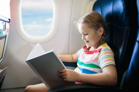 Photo pour Child in airplane. Kid with book in air plane sitting in window seat. Flight entertainment for kids. Traveling with young children. Kids fly and travel. Family vacation. Girl reading book in airplane. - image libre de droit